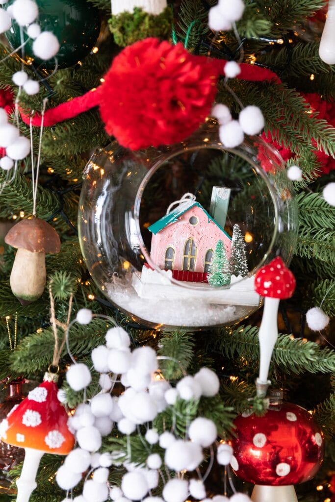 Close up view of glass dome with small pink paper house inside surrounded by mushroom ornaments on a Christmas tree