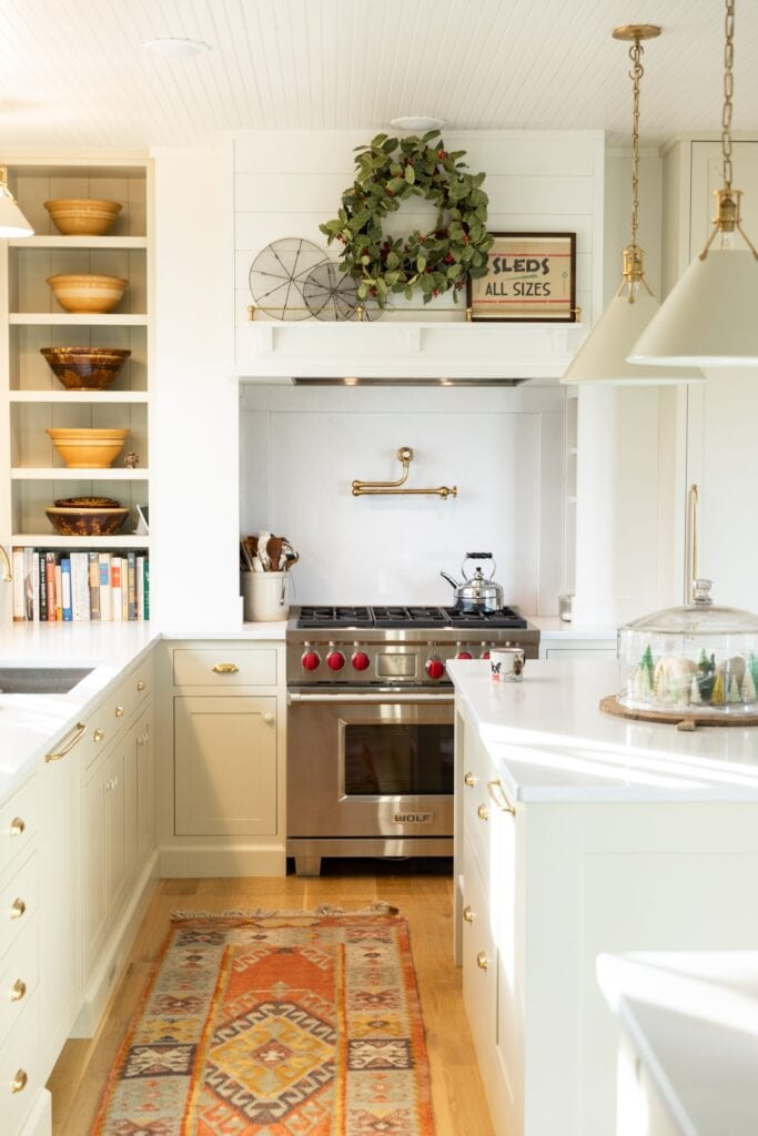 Inside of white kitchen with large range on far side of wall with white countertops and some greenery above the stove