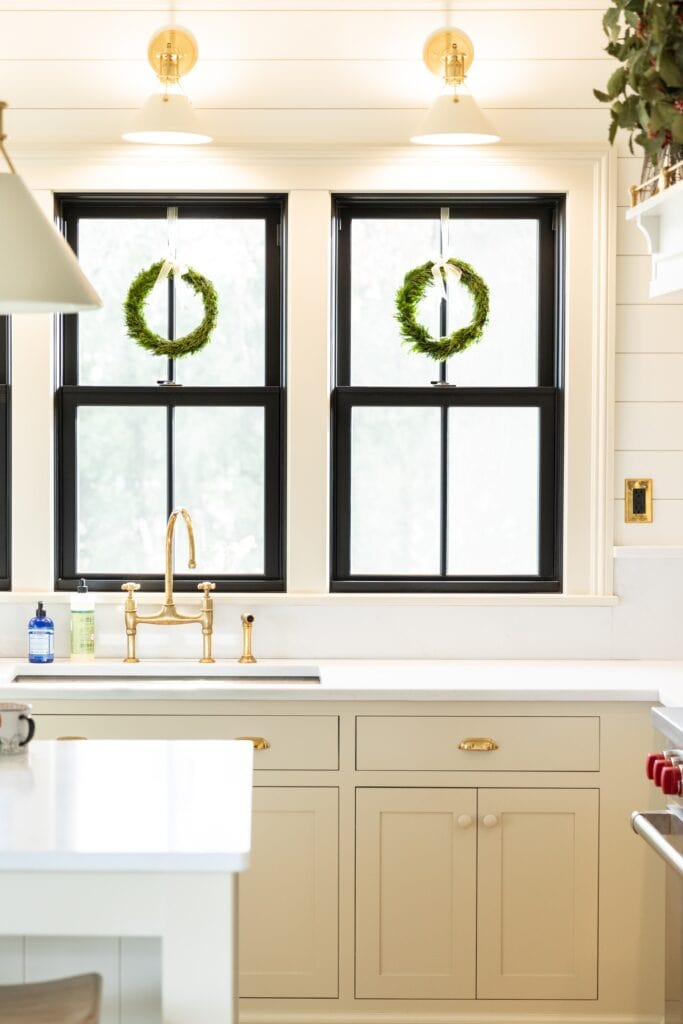 Two windows with green wreaths hanging from tops in white kitchen with white countertops and off-white cabinetry