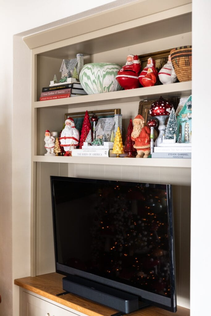 TV cabinet with shelves above adorned with Christmas Santas and glass Christmas trees
