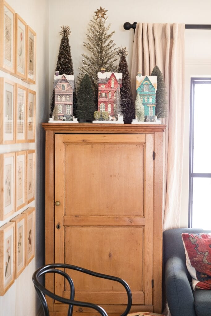Pine chest topped with tall Christmas houses along with trees behind with couch to the side and frames on the wall on the other