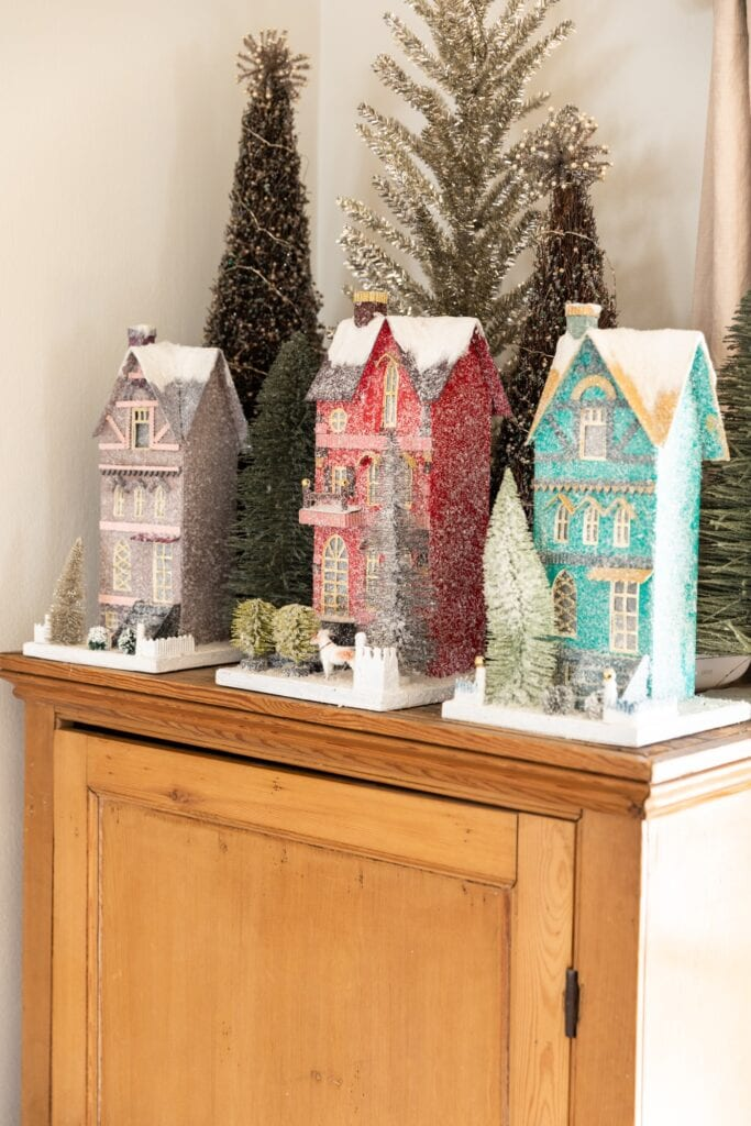 Three tall display Christmas houses with yards covered in snow sitting on top of pine dresser with trees in background