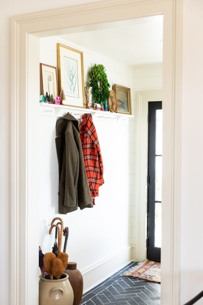 Looking into an entryway with black tile floor with pegs on the wall and coats hanging up with shelves adorned with Christmas decor