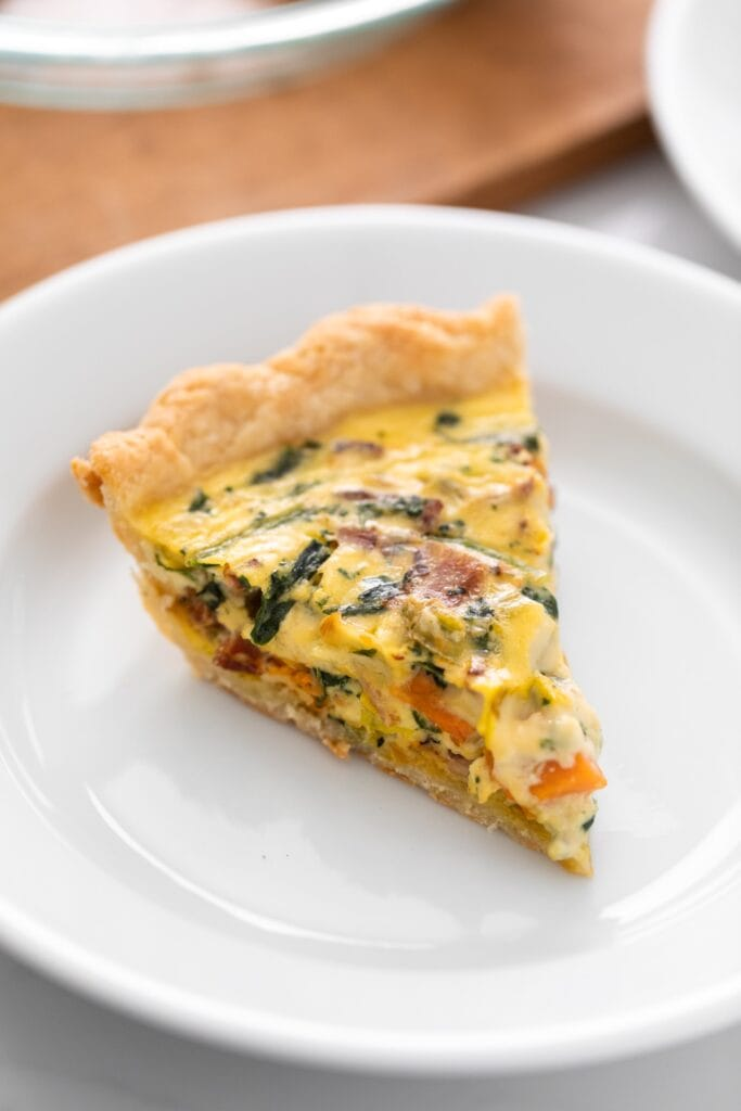 Slice of yellow colored quiche sitting on white plate with wood surface in background