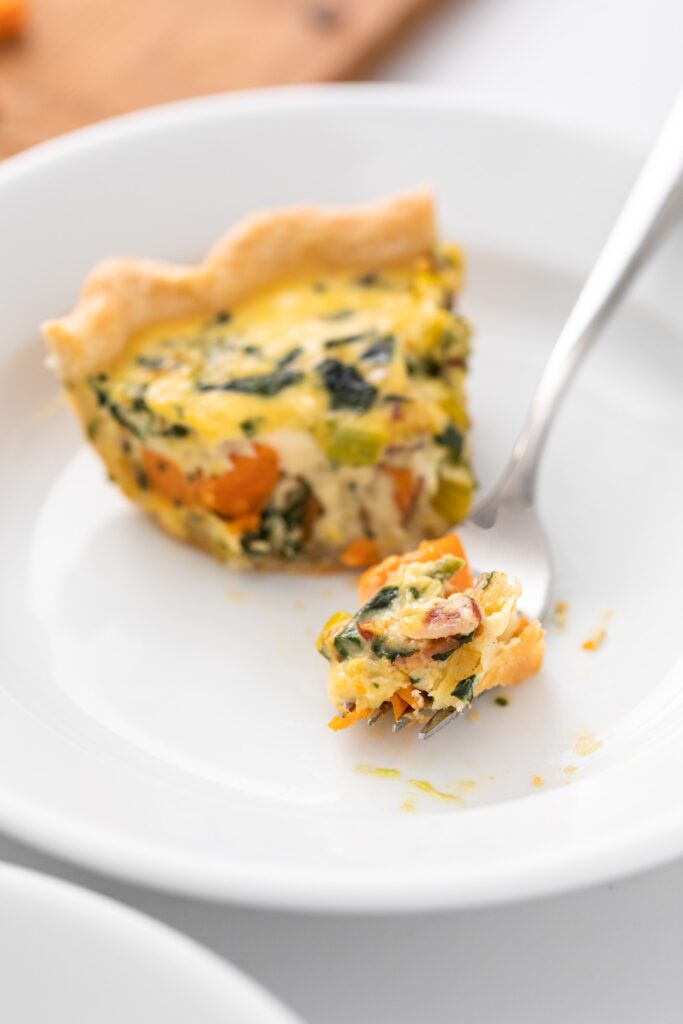 White plate containing piece of quiche with piece cut out sitting on fork