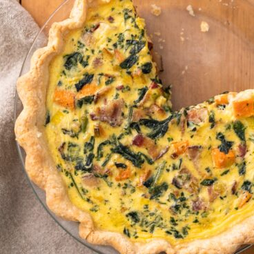 Top down view of yellow colored sweet potato quiche dotted with spinach and pieces of bacon all on wood surface