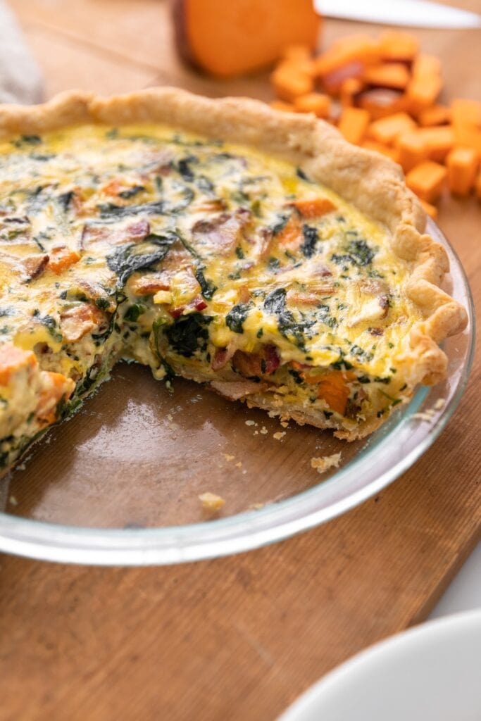 Glass pie plate containing yellow quiche with several pieces cut out with extra chunks of sweet potato in the background all on wooden surface