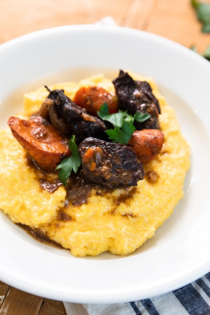 White plate filled with yellow polenta and topped with Beef Bourguignon along with carrots and topped with parsley