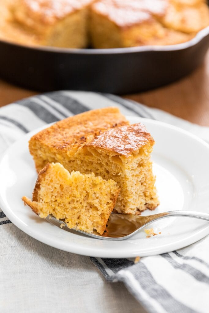 Piece of yellow cornbread sitting on white plate with fork holding piece of bread with extra cornbread in background
