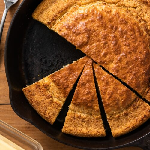 Top down view of slices of cornbread sitting in black cast iron skillet with pat of butter on the side all on wood surface