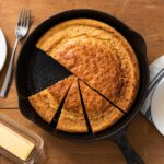 Top down view of black cast iron skillet containing baked cornbread with white plates sitting beside filled with slices of the bread along with stick of butter all on wood surface