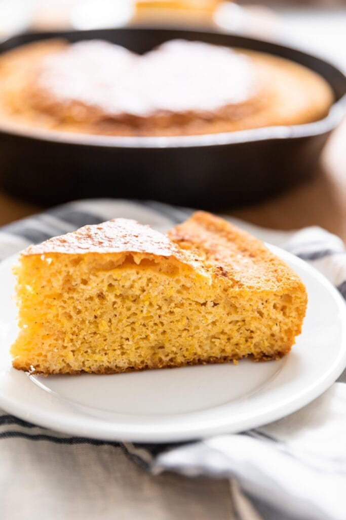 Side view of piece of yellow cornbread sitting on white plate with rest of cornbread in skillet in background