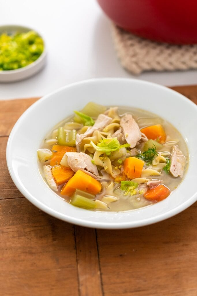 White bowl filled with broth-filled soup with pieces of celery and carrots and chicken all on wood surface with red bowl in background