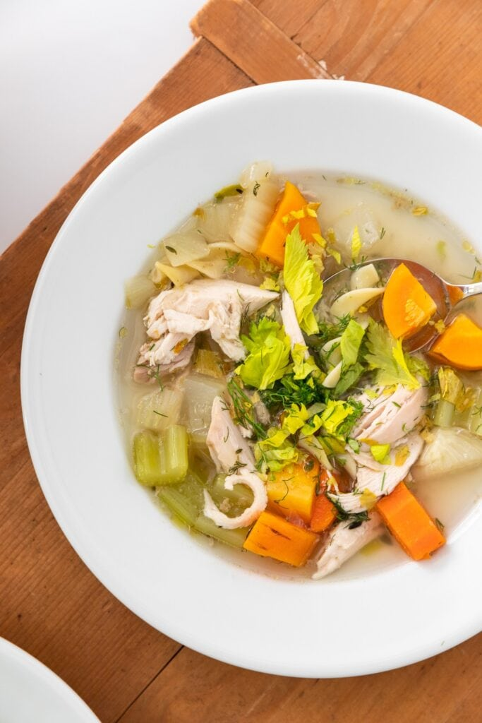 Top down view of white bowl filled with broth filled chicken noodle soup with chunks of carrots and celery on wood surface