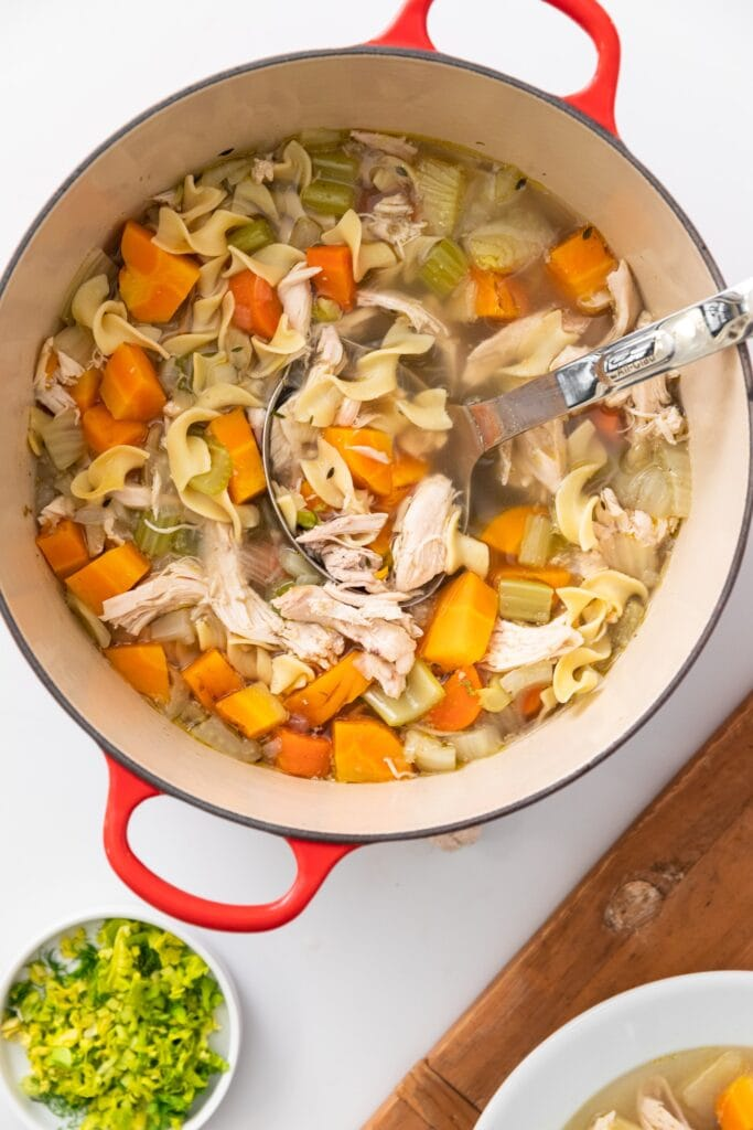 Top down view of red colored bowl filled with chicken noodle soup filled with chunks of chicken and carrots and celery with wood board all on white countertop