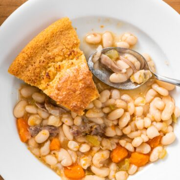 Top down view of white bean and ham soup with slices of cornbread sitting amongst soup all on white bowl