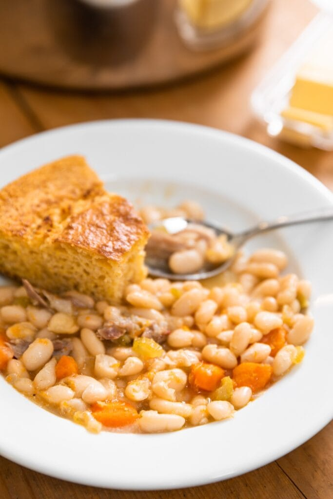 White bowl holding yellow colored bean soup with pieces of ham and carrots with slice of cornbread