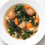 Top down view of white bowl holding light brown soup filled with kale and carrots and meatballs