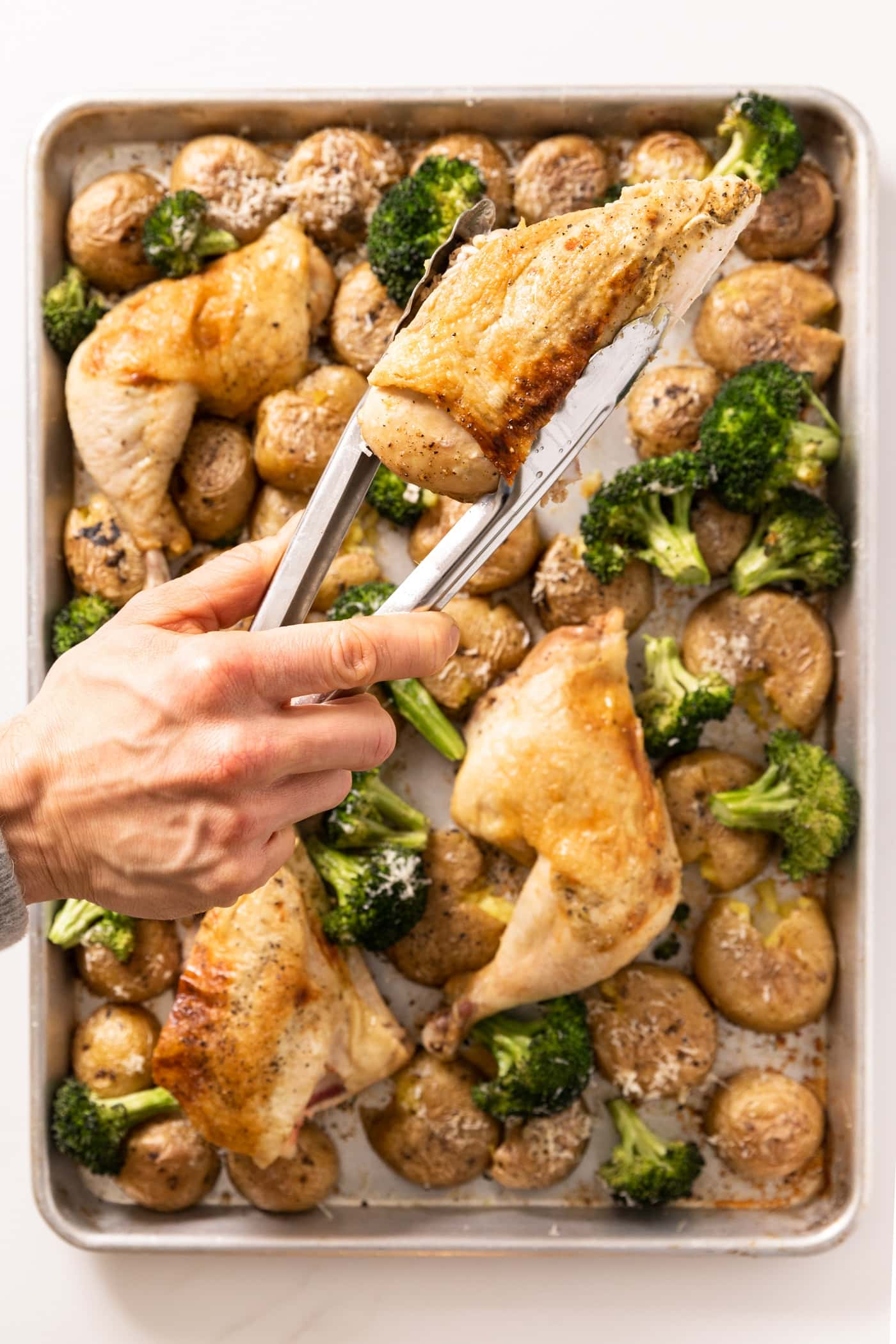 Top down view of hand holding roasted chicken breast over a sheet pan filled with other chicken breasts and broccoli and potatoes
