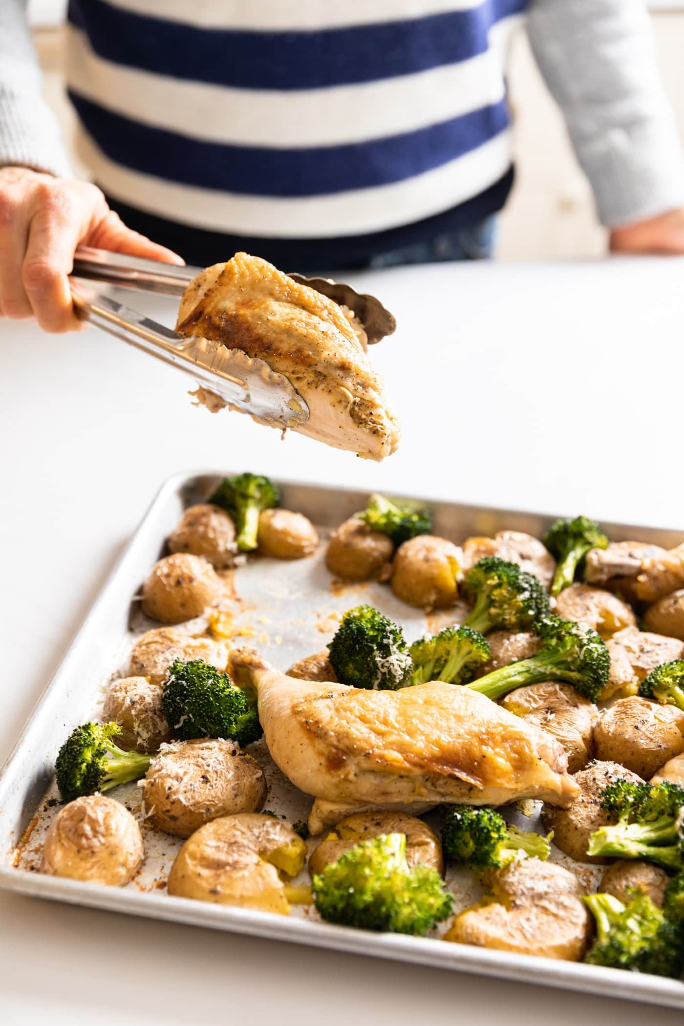Hand holding roasted chicken breast in tongs over a sheet pan with other chicken breasts and broccoli and potatoes