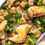 Top down view of roasted chicken breasts sitting amongst broccoli and potatoes all on sheet pan