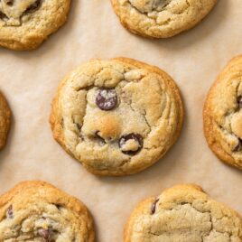 Top down view of chocolate chip cookies sitting on brown colored parchment paper