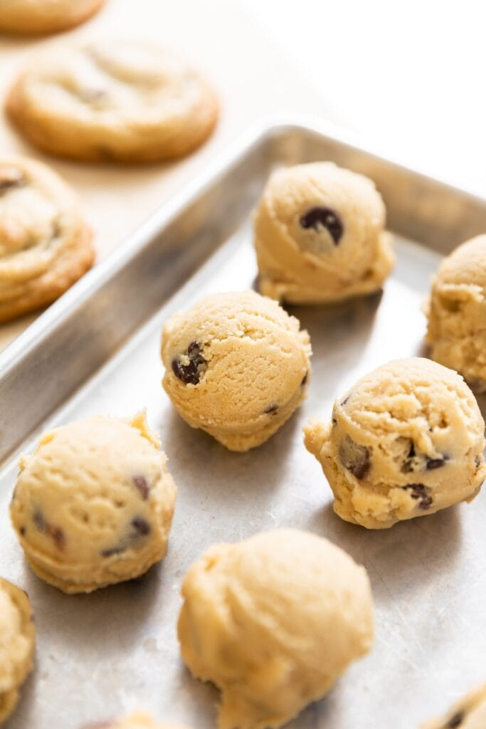 Unbaked cookie dough balls sitting on silver baking dish with some baked cookies in background