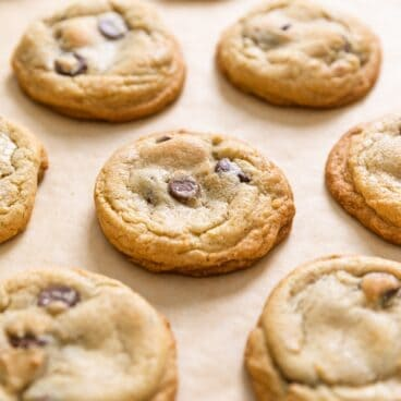 Multiple yellow colored chocolate chip cookies sitting on brown colored parchment paper