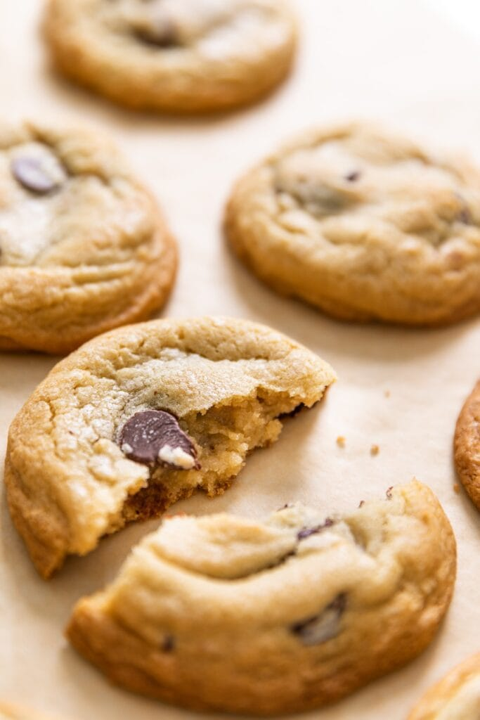 Lightly browned chocolate chip cookie broken apart and sitting on brown piece of parchment with extra cookies in background