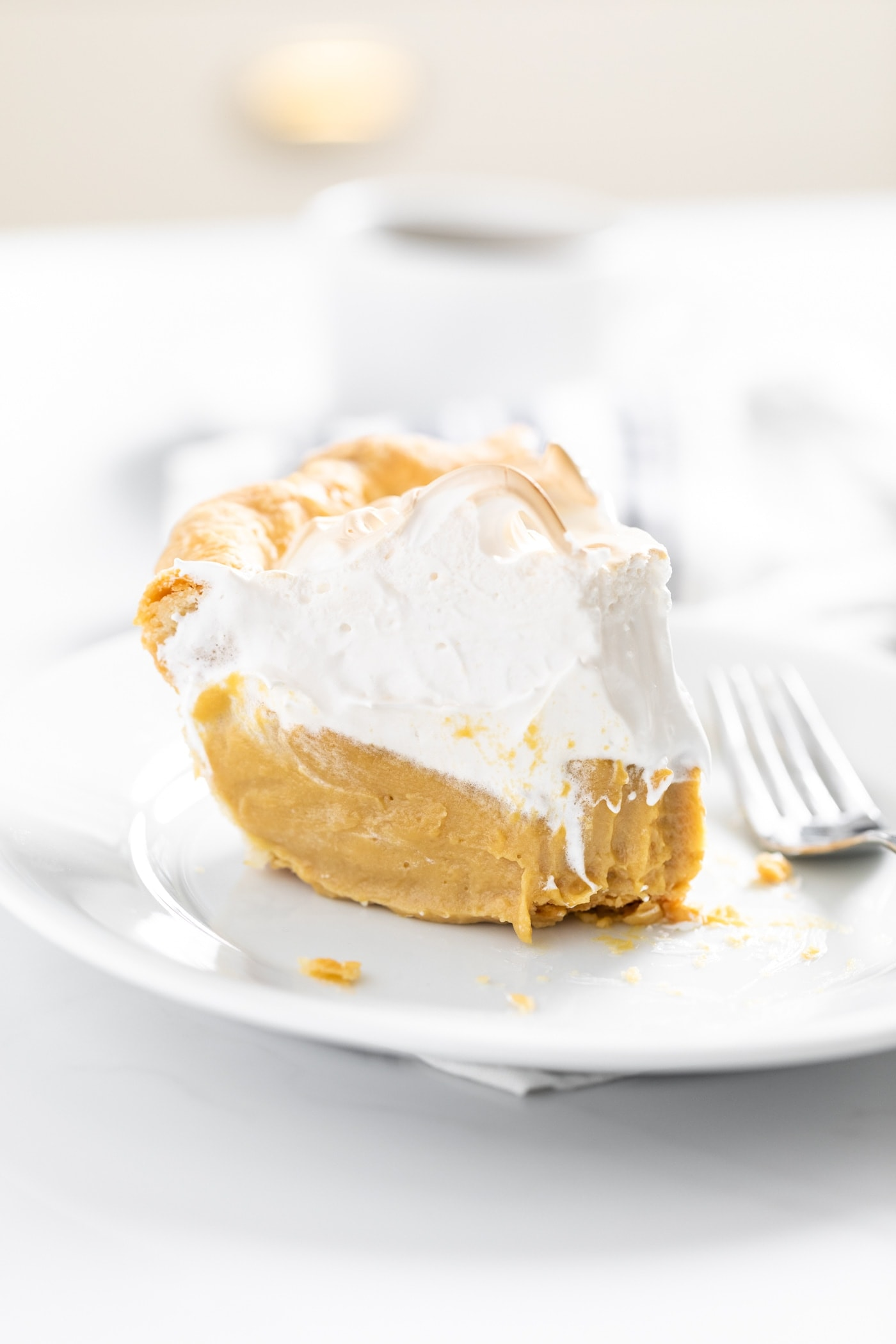 Close up view of piece of butterscotch pie topped with creme brûlée frosting sitting on white plate all on white countertop with mug in background
