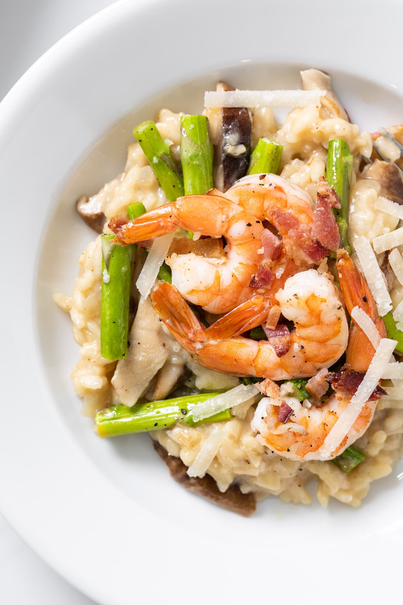 Top down close up view of risotto sitting on white plate topped with asparagus and pink colored shrimp pieces