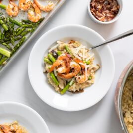 Top down view of white bowl filled with creamy light brown colored risotto with sheet pan filled with asparagus and shrimp to the side