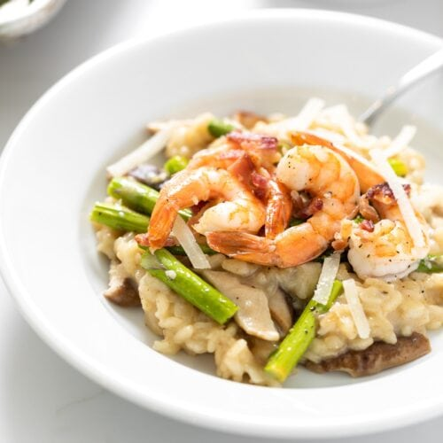 White bowl filled with Parmesan risotto and topped with shrimp and asparagus with sheet pan in background all on white surface