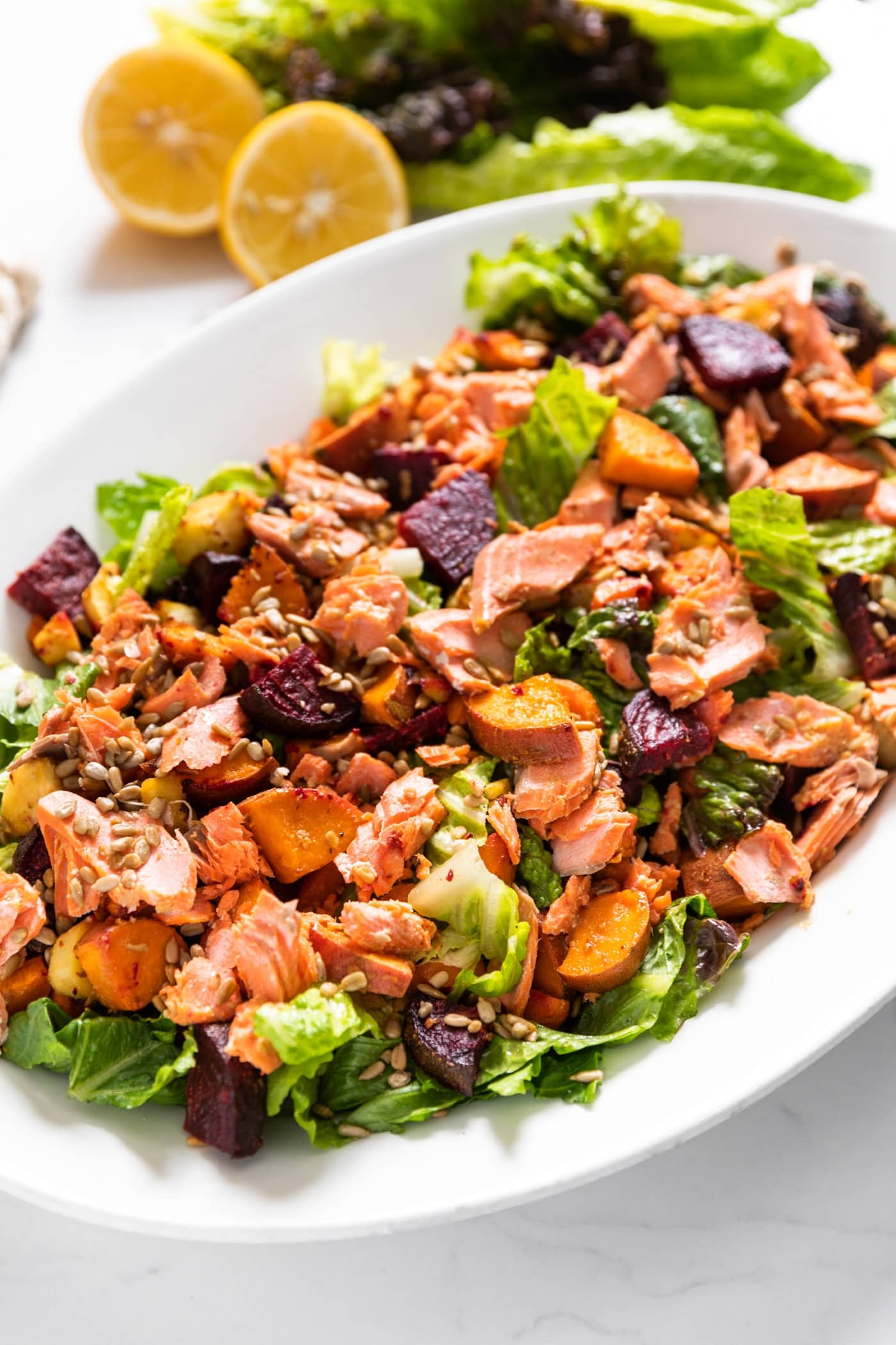 Large white platter sitting on white countertop filled with salad greens topped with beets and carrots and sweet potatoes and salmon with cut lemons in background