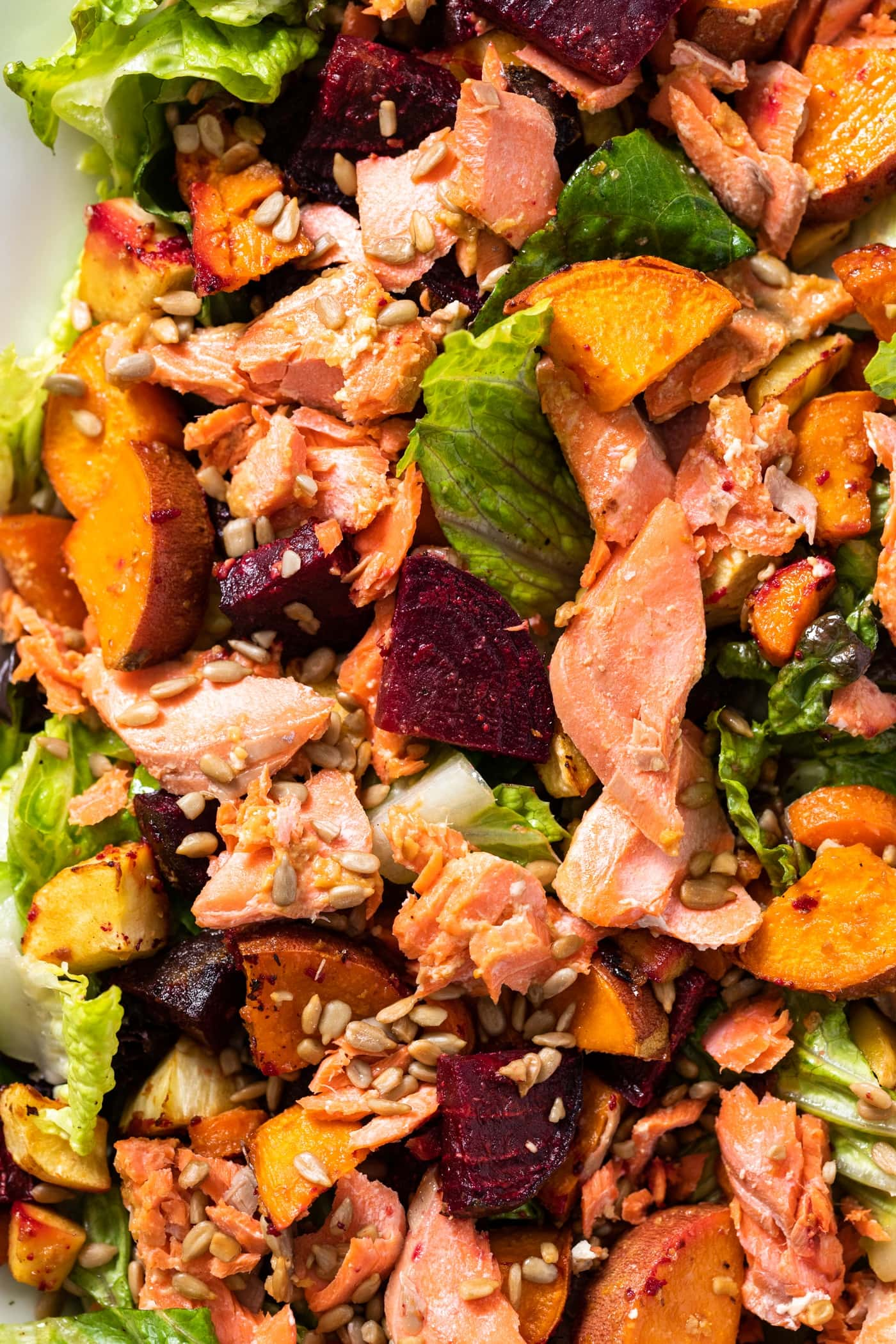 Close up top down view of salmon sitting on bed of green lettuce surrounded by orange colored sweet potatoes and topped with sunflower seeds