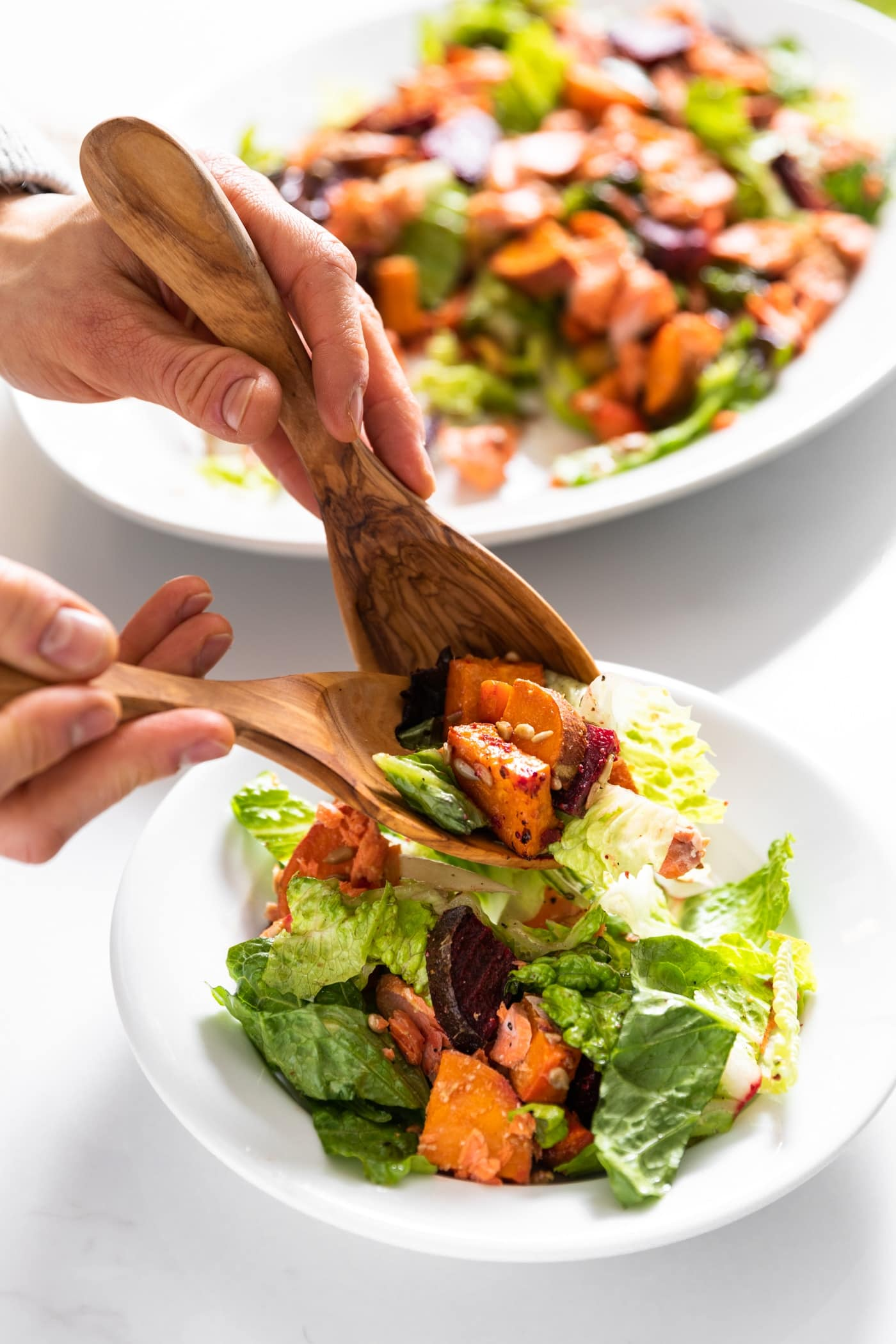 Two hands holding tongs spoon salad onto white plate from salad sitting in white plate behind