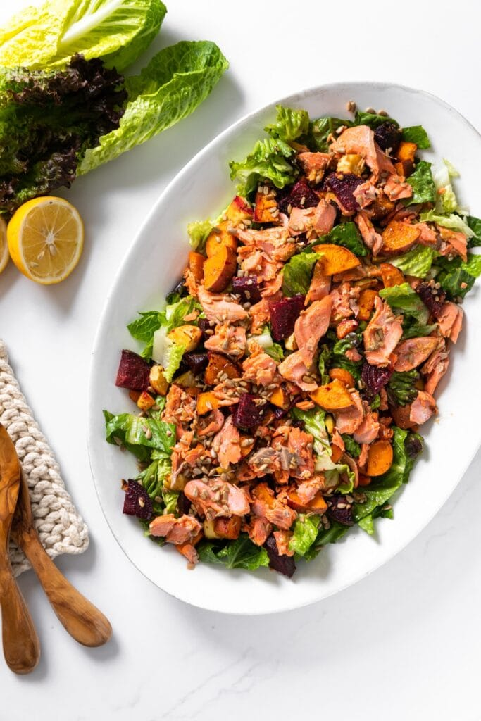 Top down view of white platter filled with green salad topped with pink salmon and roasted vegetables with lemon and extra lettuce to the side all on white counntertop