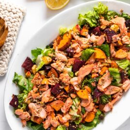 Top down view of salmon salad sitting on white platter with serving spoons sitting beside