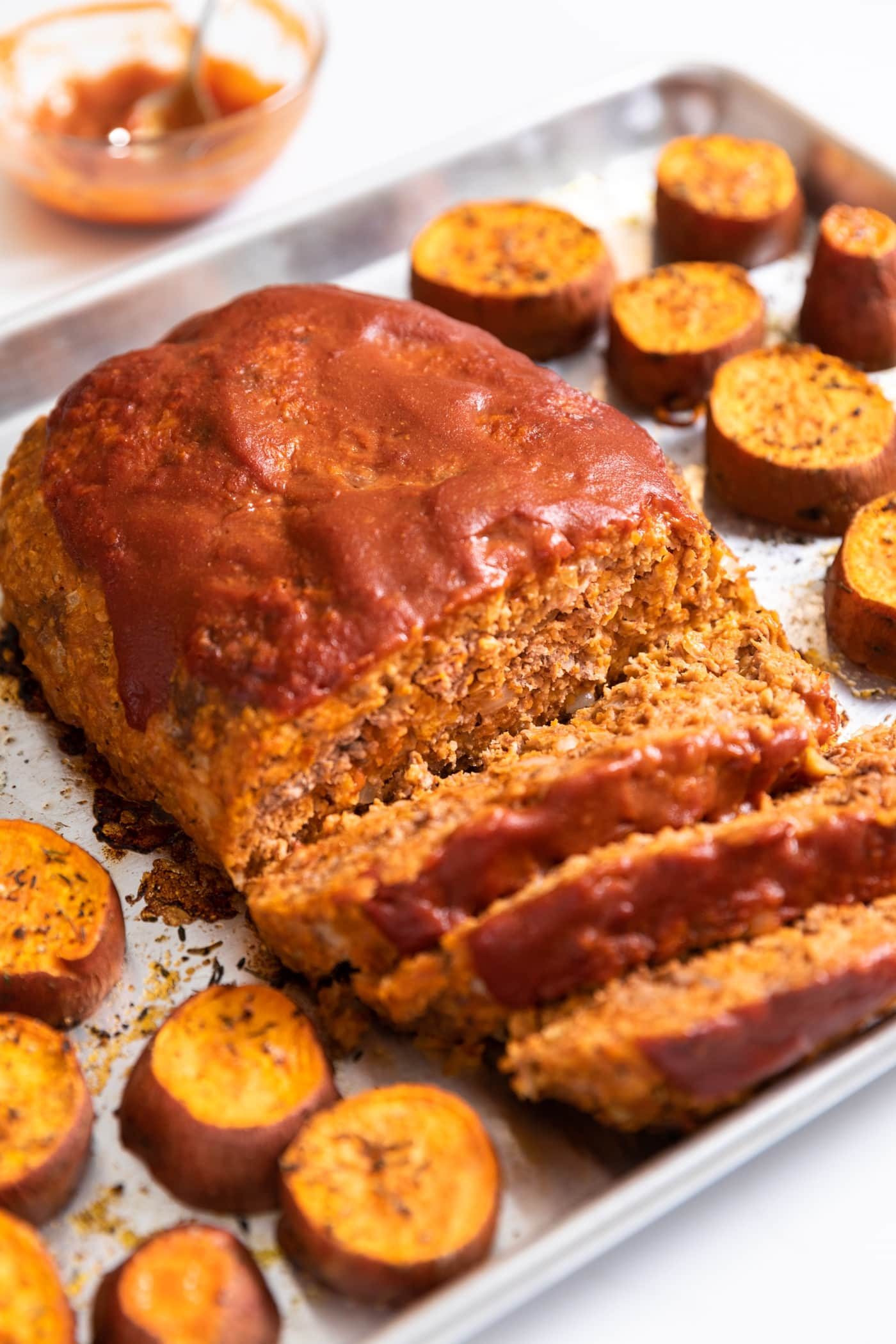 Meatloaf covered with red ketchup on top with slices laying on sheet pan with orange colored sweet potatoes all around