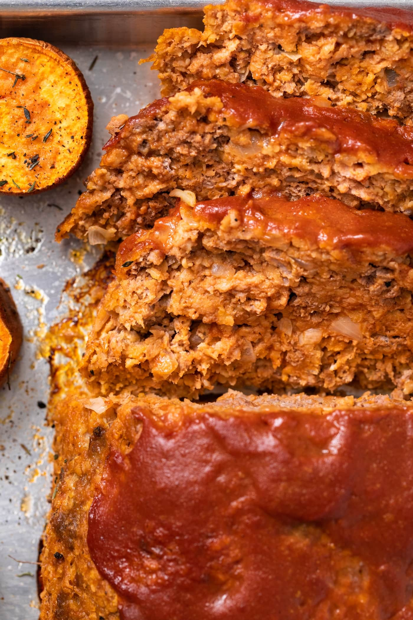 Close up top down view of slices of meatloaf laying on sides of sheet pan with one slice or orange colored sweet potato