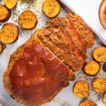 Top down view of meatloaf topped with red ketchup sitting on sheet pan with slices of orange sweet potato freshly baked from the oven