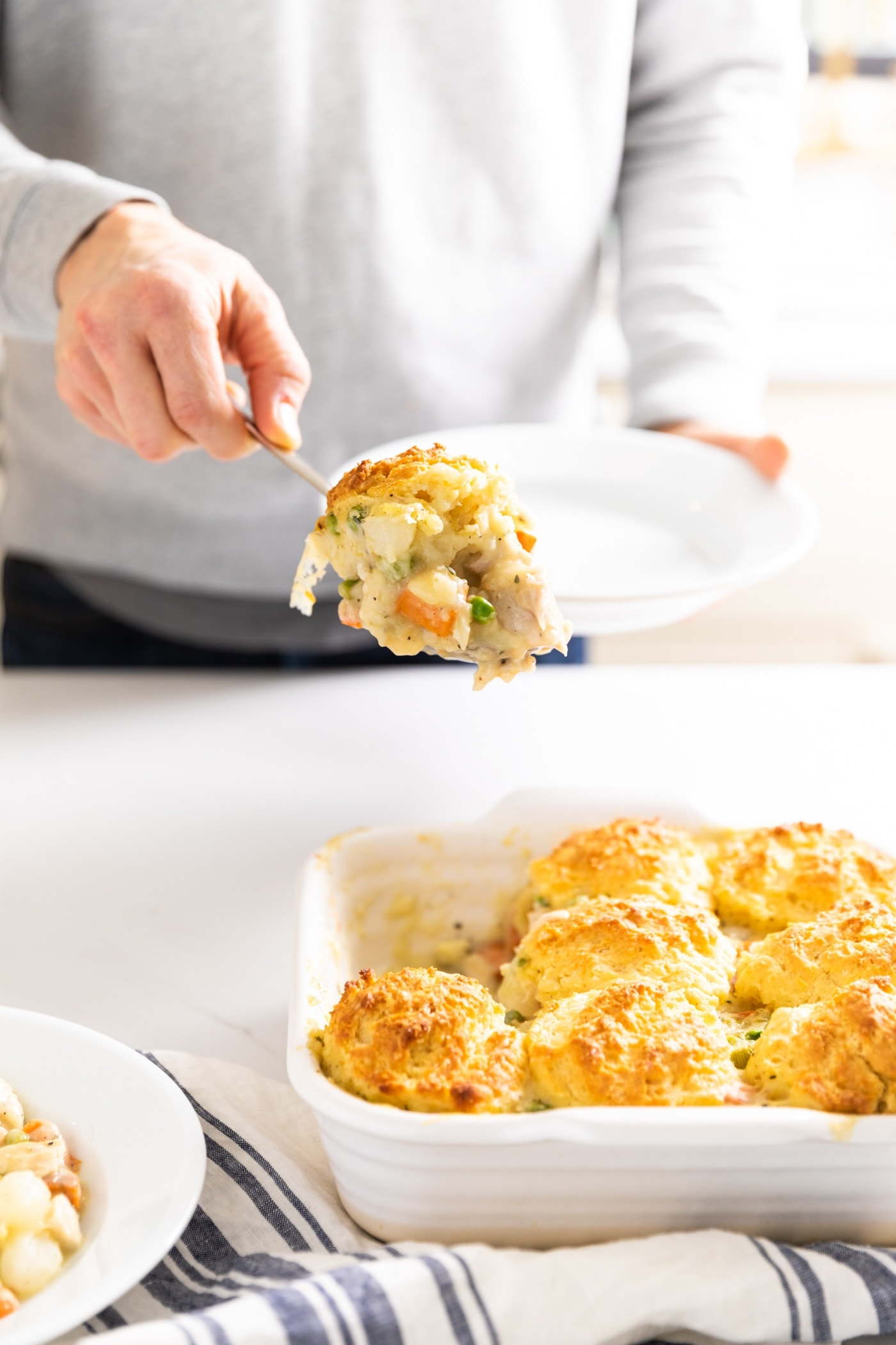 Hand holding scoop of chicken pot pie mixture with biscuit on top with container of biscuits underneath