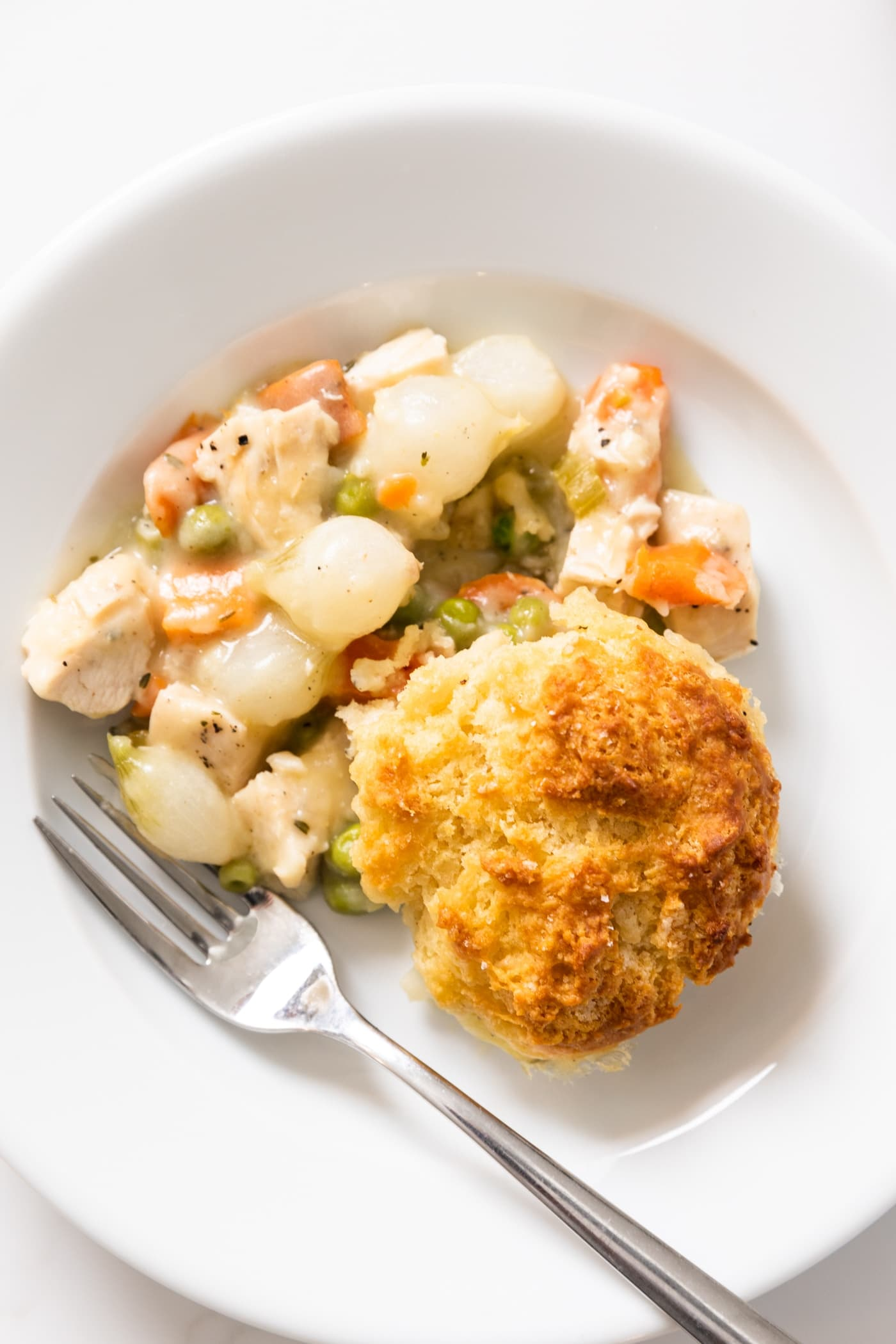 Top down view of white plate holding a thickened sauce with vegetables sitting in mixture topped with a biscuit