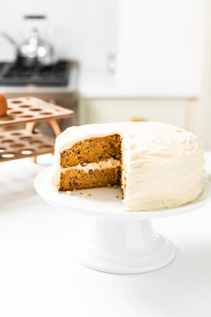 White cake plate with carrot cake with slices missing all sitting on white countertop with egg rack in background