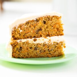 Slice of layered carrot cake sitting on green plate on a white countertop with a white cake plate in background