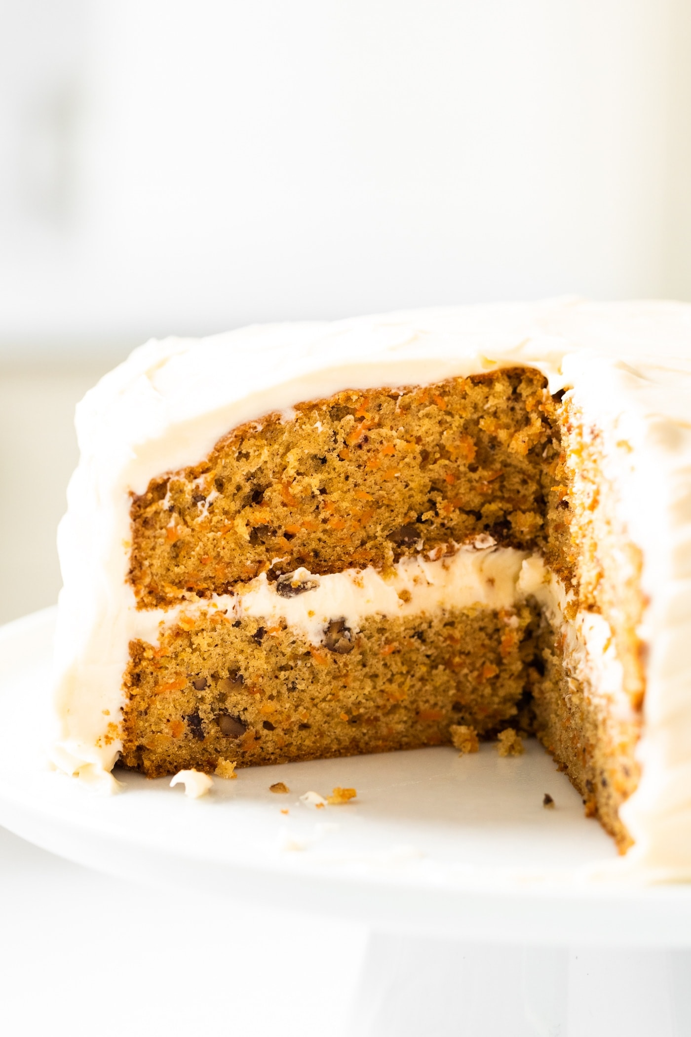 Close up view of inside of orange colored carrot cake topped with cream cheese frosting sitting on white cake plate with white background