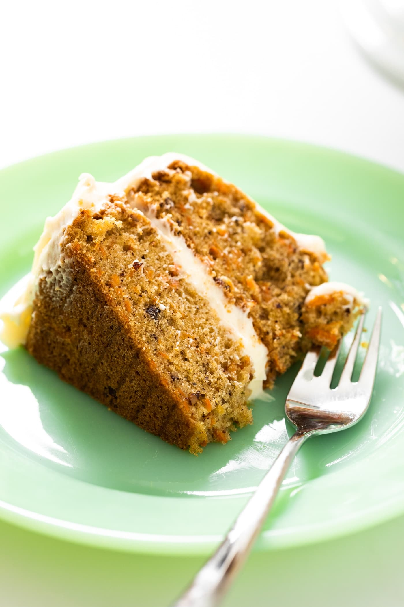 Big slice of carrot cake with two layers and white cream cheese frosting in between layers sitting on green colored place with fork