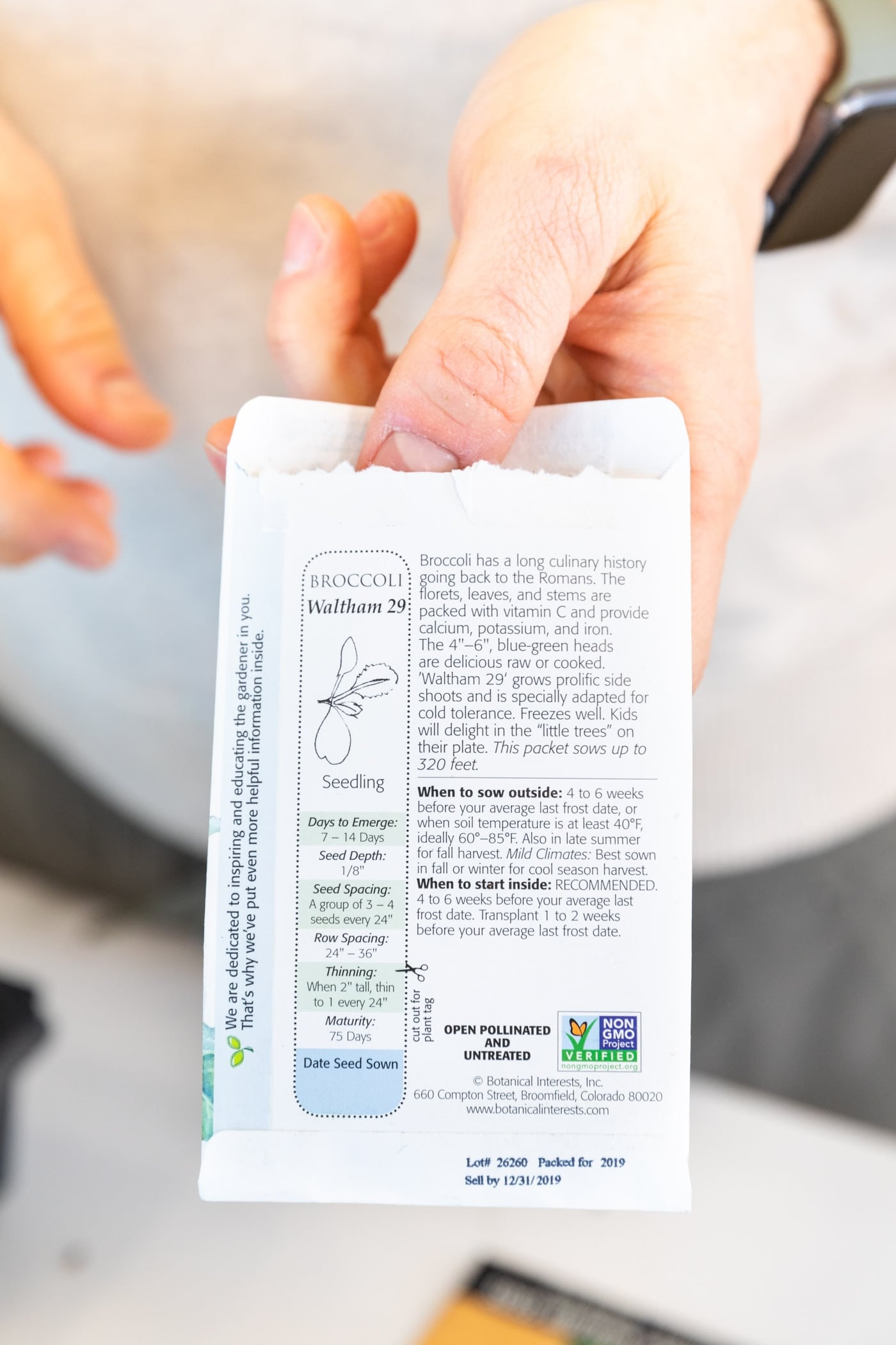 Hand holding seed packet with lots of writing on the back in front of a white countertop