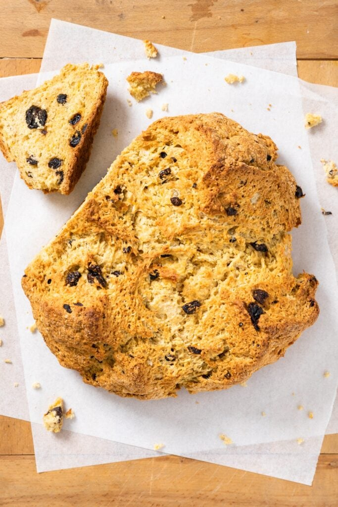 Top down view of circular brown colored loaf of Irish soda bread sitting on white parchment paper with one slice sliced off and laying to the side