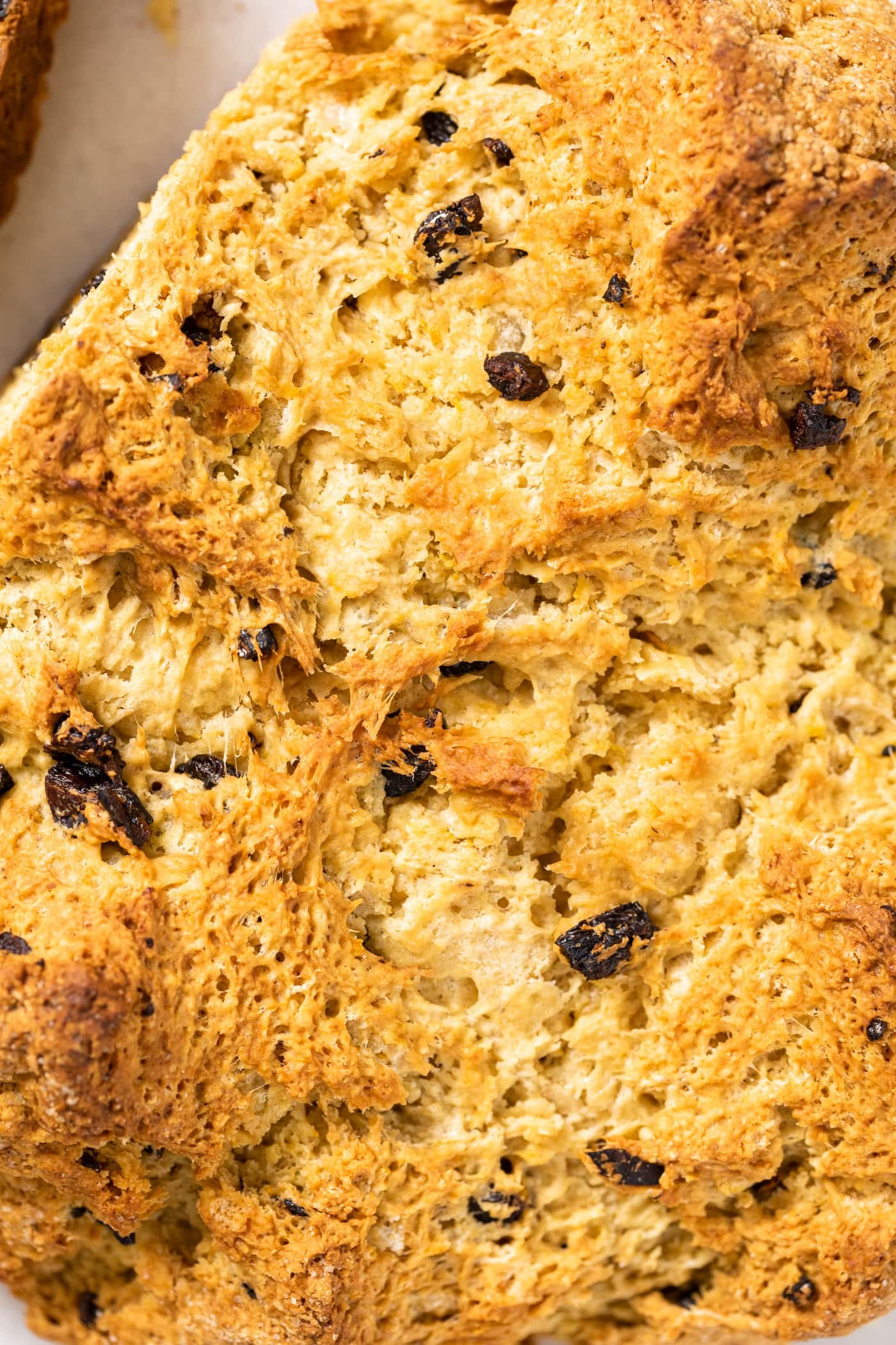 Top down view of top of Irish soda bread showing the golden texture of bread with peaks and valleys and craggy areas